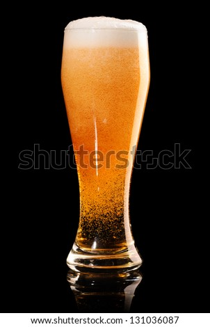 glass of fresh lager beer on black with reflection