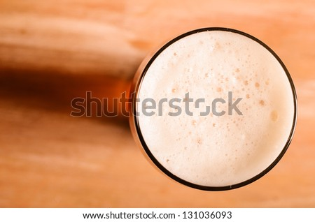 glass of fresh lager beer on wooden table