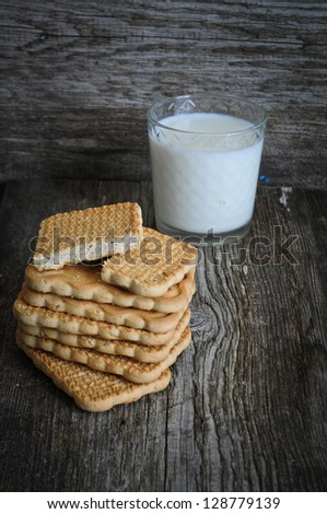 Glass of fresh milk and cookies on a wooden table
