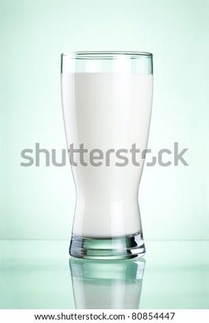 Glass of fresh milk on green background