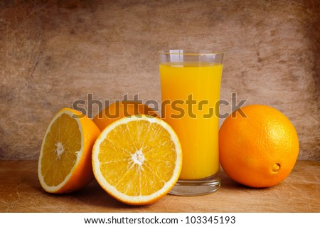 glass of fresh orange juice and oranges on a vintage wooden background