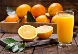 glass of fresh orange juice with fresh fruits on wooden table