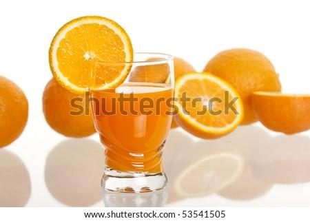 glass of fresh orange juice with orange in the background