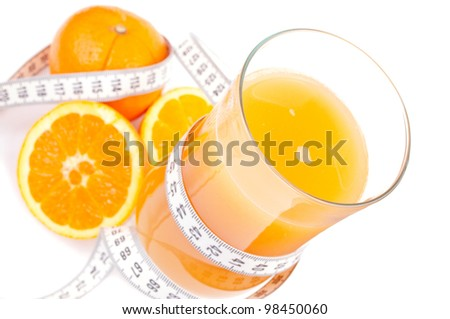 Glass of fresh orange juice, wrapped with centimeter and oranges isolated on white