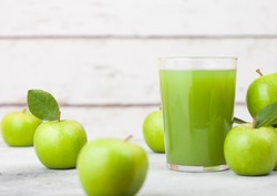 Glass of fresh organic apple juice with granny smith and british bramley apples in box on wooden background.