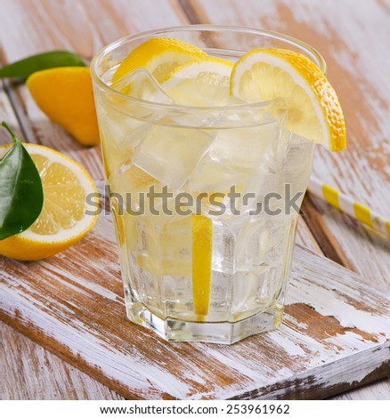 Glass of fresh water with a lemon. Selective focus