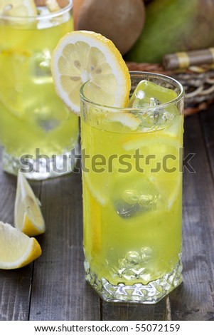 Glass of freshly made cold lemon beverage with pieces of the fruit