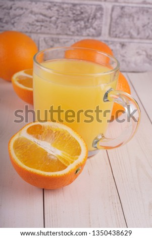 Glass of freshly squeezed orange juice standing on light background with a fresh oranges.  Healthy lifestyle concept. Copy space for text. #1350438629
