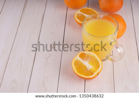 Glass of freshly squeezed orange juice standing on light background with a fresh oranges.  Healthy lifestyle concept. Copy space for text. #1350438632