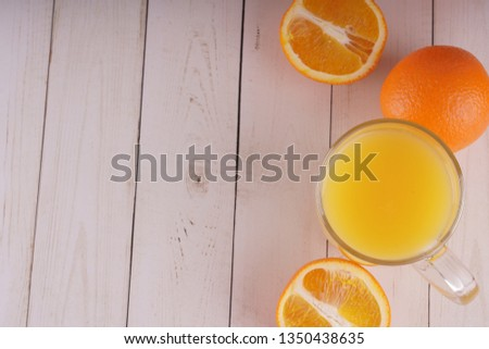 Glass of freshly squeezed orange juice standing on light background with a fresh oranges.  Healthy lifestyle concept. Copy space for text. #1350438635