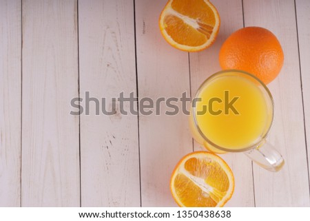 Glass of freshly squeezed orange juice standing on light background with a fresh oranges.  Healthy lifestyle concept. Copy space for text. #1350438638