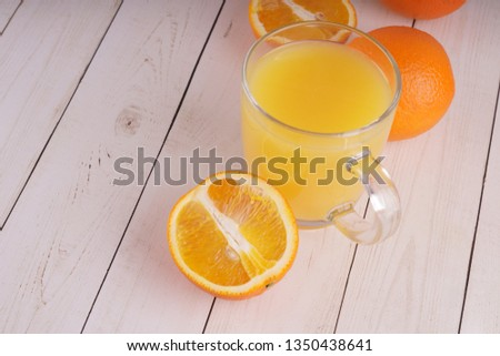 Glass of freshly squeezed orange juice standing on light background with a fresh oranges.  Healthy lifestyle concept. Copy space for text. #1350438641
