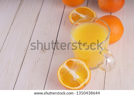 Glass of freshly squeezed orange juice standing on light background with a fresh oranges.  Healthy lifestyle concept. Copy space for text. #1350438644
