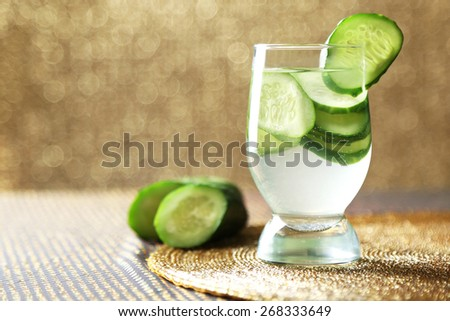 Glass of freshness water with cucumber, on bright background
