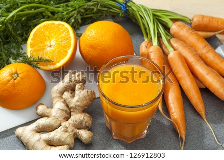 Glass of fruit juice with orange, carrots and ginger on a cutting board