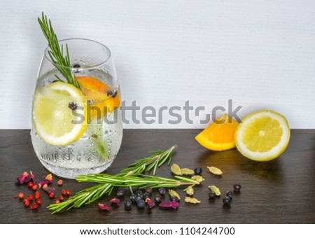 Glass of Gin and Tonic Garnished with Ice, Orange, Lemon and Rosemary on Wooden Table Surrounded with Botanicals