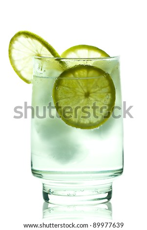Glass of gin and tonic with ice cubes and lime slices. isolated on white