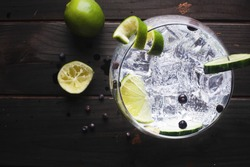 Glass of gin tonic with cucumber, lime and ice over a wooden table