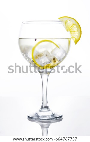 Glass of gin tonic with lemon on white background #664767757