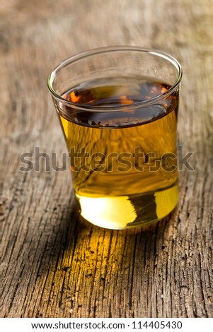 glass of golden alcohol on wooden table