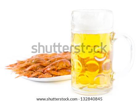 Glass of golden frothy beer served with a seafood platter of delicious cooked whole unshelled prawns on a white background