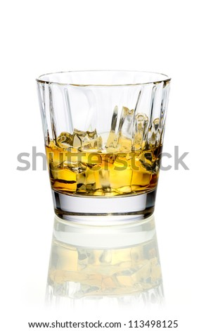 Glass of golden whiskey or brandy served on ice on a reflective white surface