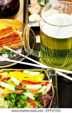 glass of green beer and plates with different food in japanese restaurant