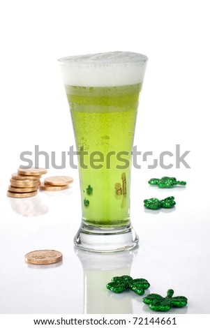Glass of green beer for St Patrick's Day surrounded with gold coins and shamrock ornament