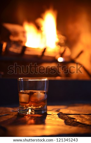 glass of hard liquor with ice cubes in front of the fireplace at night