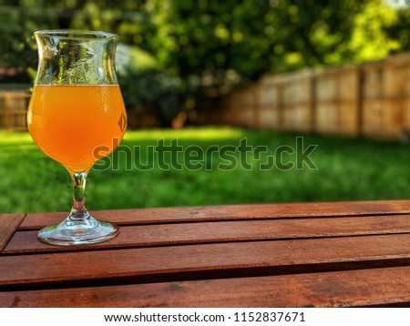 Glass of hazy beer on outdoor wooden table in Indiana backyard