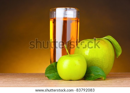 Glass of healthy fresh juice of apples on brown background