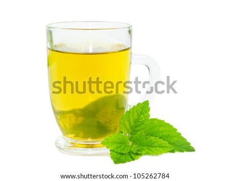 Glass of herbal lemon balm tisane or tea with fresh green leaves on a white studio bacground