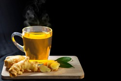 Glass of hot ginger tea with sliced ginger rhizomes (roots) and leaves placed on separate planks on a black background.