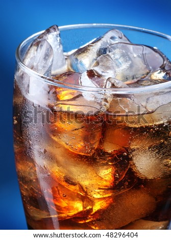 Glass of ice cola on a blue background