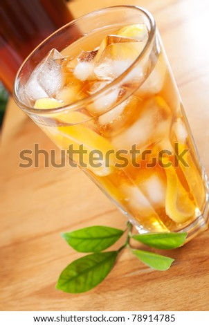 glass of ice tea with lemon and pitcher on a background