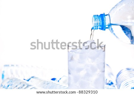 Glass of ice water being filled with a water bottle - stock photo