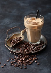 Glass of iced coffee drink with straw on tray with coffee beans and scoop on black background. Top view