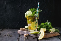 Glass of Iced green tea with lime, lemon, mint and sugar cubes on wooden chopping board over old wooden table. Dark rustic style.