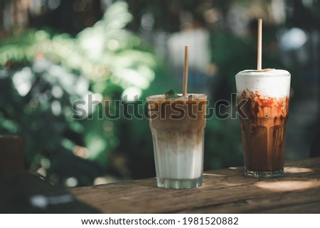 Glass of iced latte coffee and iced mocha placed on wood table with garden background at outdoor cafe Stock fotó ©