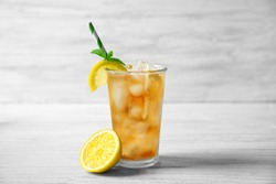 Glass of iced tea with lemon slices and mint on white wooden table