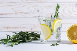 Glass of icy organic lemonade with rosemary on the table. Healthy detox drink on the table close up.