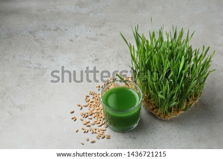 Glass of juice, sprouted wheat grass and grains on grey stone background. Space for text #1436721215