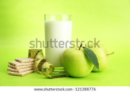 Glass of kefir, apple, crispbreads and measuring tape, on green background