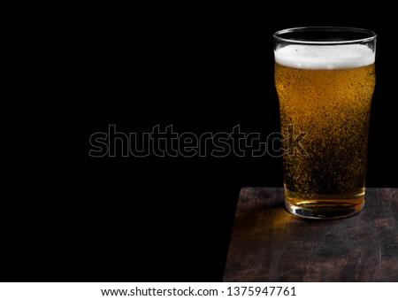 Glass of lager beer with foam and bubbles on vintage wooden board on black. Space for text #1375947761