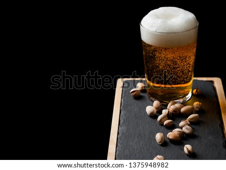 Glass of lager beer with pistachios nuts on stone board on black background. #1375948982