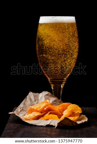 Glass of lager beer with potato crisps snack on vintage wooden board on black background. #1375947770