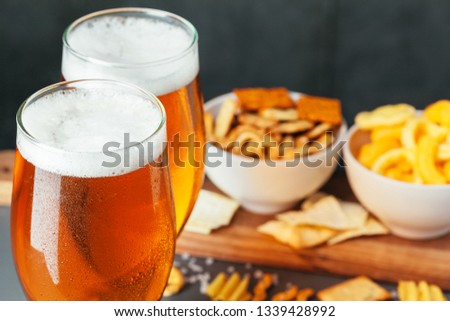 Glass of lager beer with snack bowls on dark stone background #1339428992
