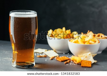 Glass of lager beer with snack bowls on dark stone background #1341832583