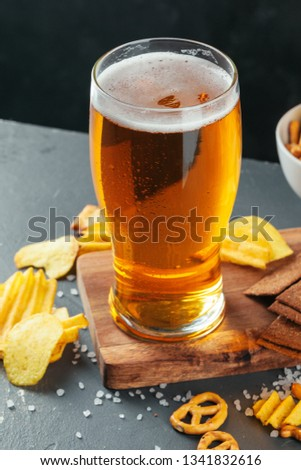 Glass of lager beer with snack bowls on dark stone background #1341832616