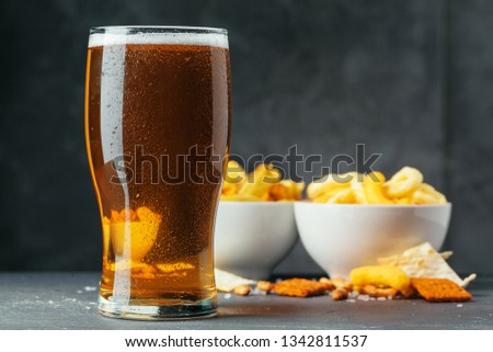 Glass of lager beer with snack bowls on dark stone background #1342811537